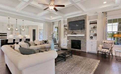 Model living room with TV, fire place, and white furniture.