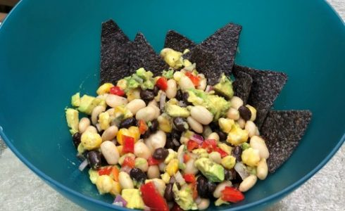 Blue bowl of dip with avocado, beans, and tortilla chips.