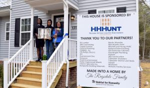 Family standing in front of HHHunt Sponsored home in partnership with Habitat for Humanity.