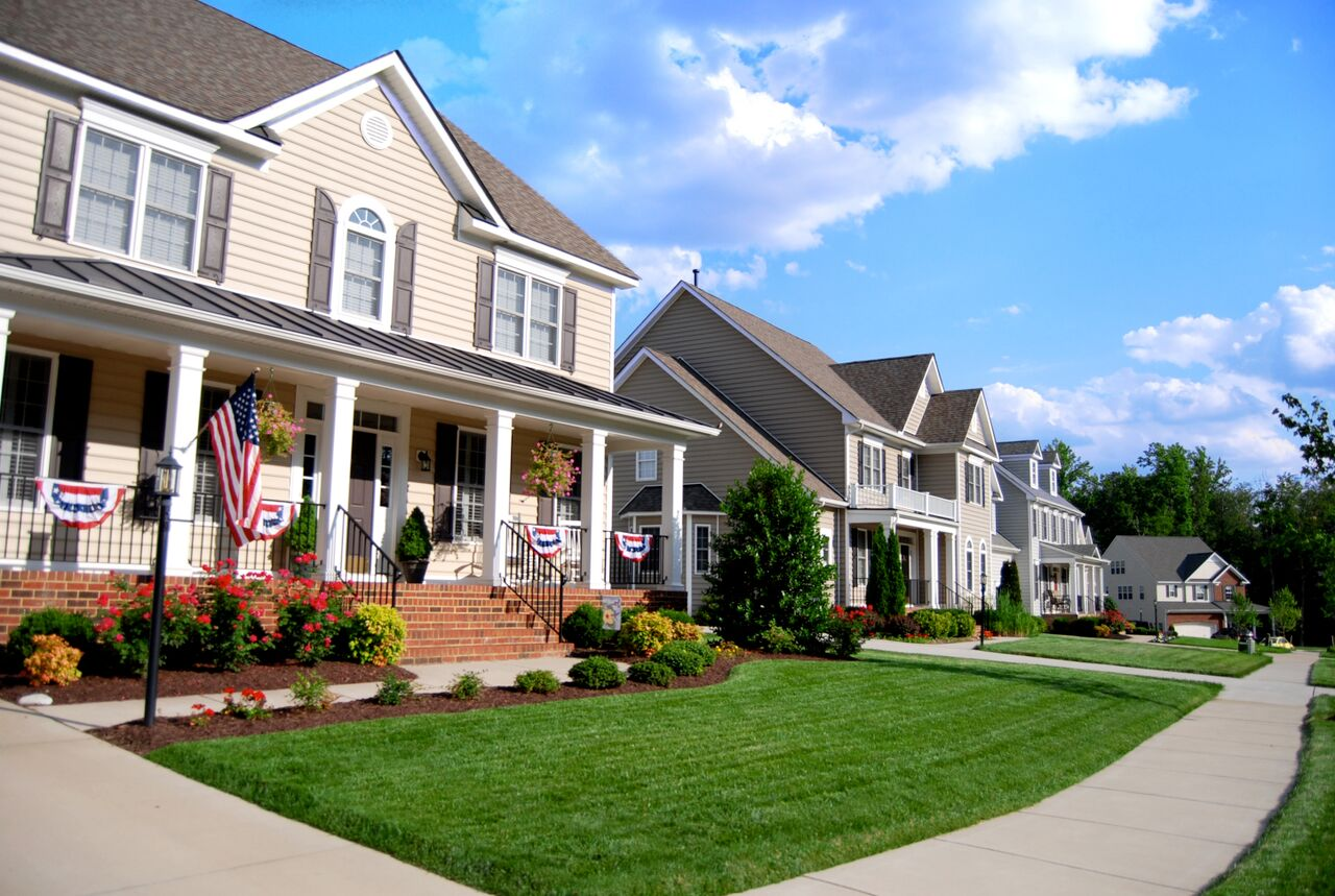 Single-family homes with patriotic decorations and neatly trim lawns.