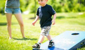 Young boy walking on HHHunt branded cornhole board.