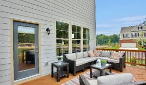 Deck with patio furniture with white cushions, floral pillows, and glass tables.