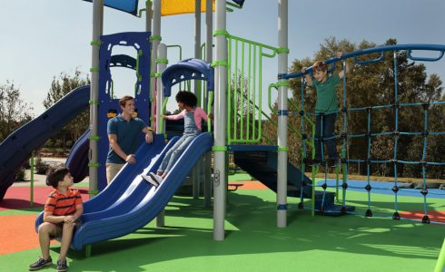 Young, diverse family playing in a park slide.