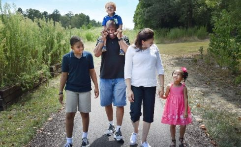 Young diverse family on walking trail and smiling.