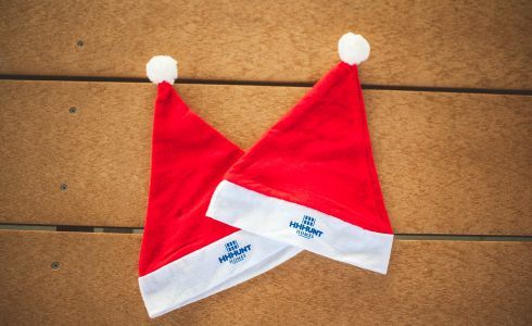 HHHunt Homes branded Santa hats on wooden table.