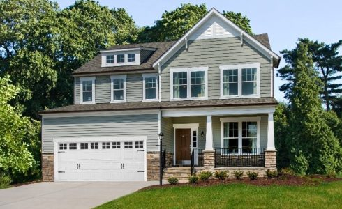 Model single-family home with 2-car garage on large wooded lot.