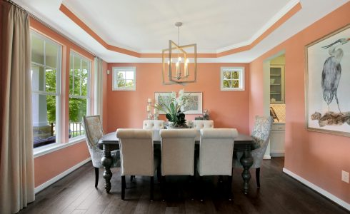 Model dining room with contemporary wall art and ornate dining furniture.