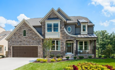 Large home with 2-car garage and primarily stone facade and large windows.