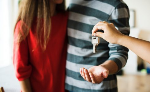 Woman in red shirt and man in green stripes receiving keys to their new home.
