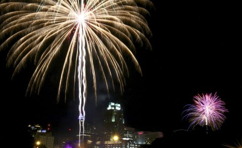 Fireworks going off with cityscape in the background.