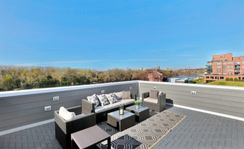 patio furniture on rooftop overlooking river from