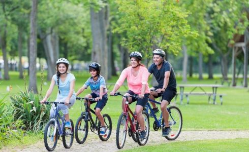 family of four biking on path in park