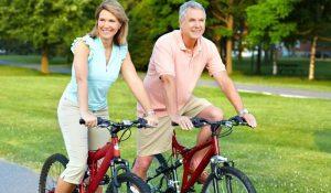 Older couple biking on path