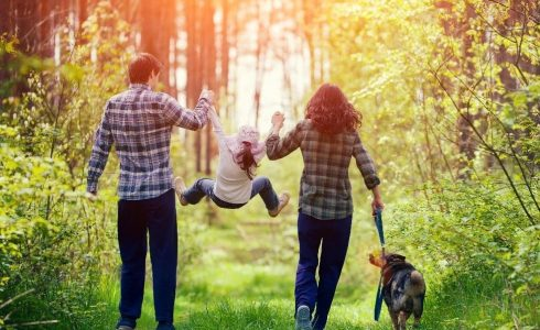 family with child and dog walking through wooded area