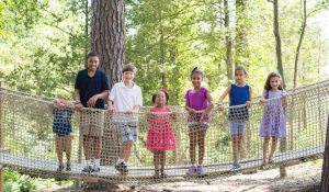 children on rope bridge in wooded area during summer