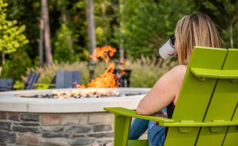 woman drinking coffee sitting outdoors looking at firepit