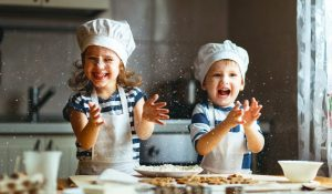two children cooking in kitchen in chefs hats