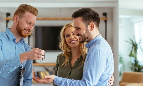 man giving keys to young couple inside of home