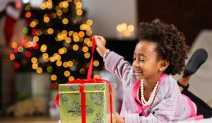 child opening gift by Christmas tree