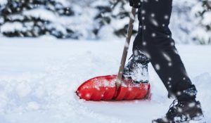 person shoveling snow with red shovel