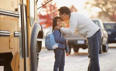 father kissing young daughter as she's getting on school bus