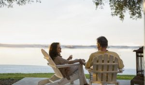 couple sitting outdoors on porch by lake