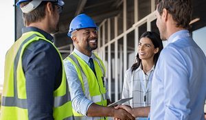 Home Construction man in hard hat shaking hands with customer