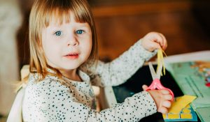 young girl cutting paper with scissors crafting