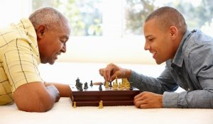 older and younger man playing chess
