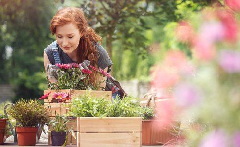 woman smelling flowers in yard spring summer garden