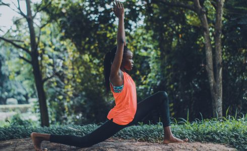 woman in orange top doing yoga outdoors spring summer exercise