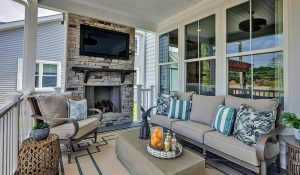 porch with outdoor fireplace in the cove at giles farm by HHHunt Homes